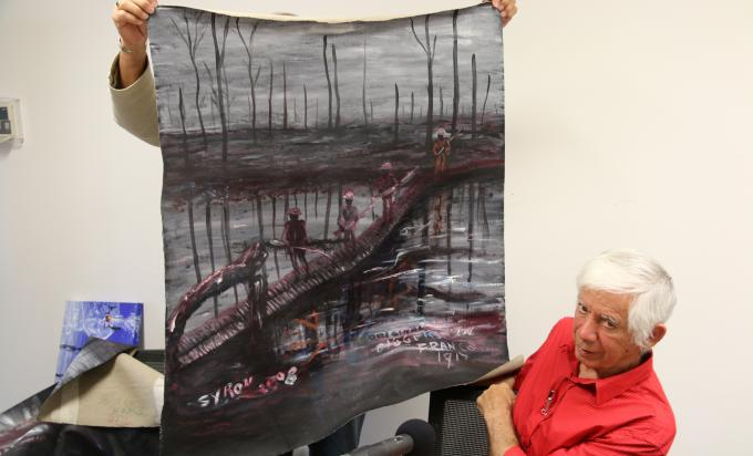 Gordon Syron showing one of his paintings depicting war
